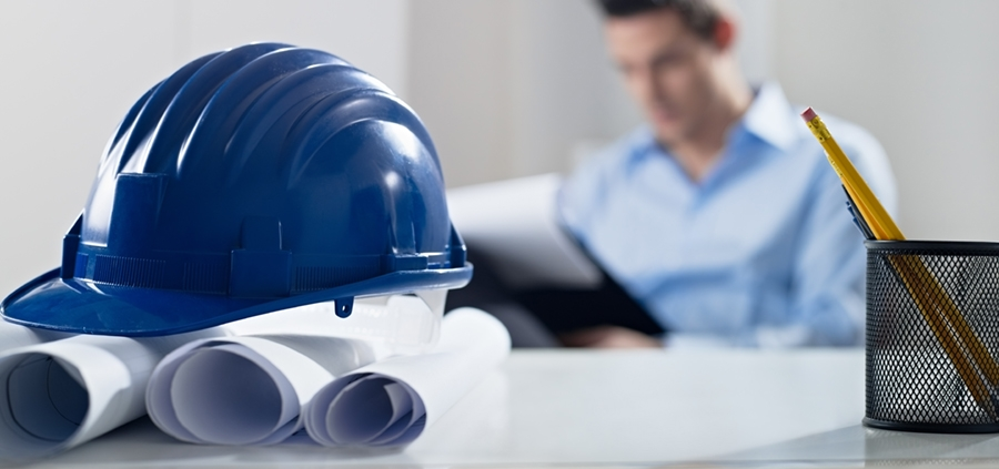 Hardhat and blueprint on desk, with architect in background